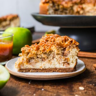 Caramel Apple Crumb Cheesecake slice on plate with caramel drizzle on top
