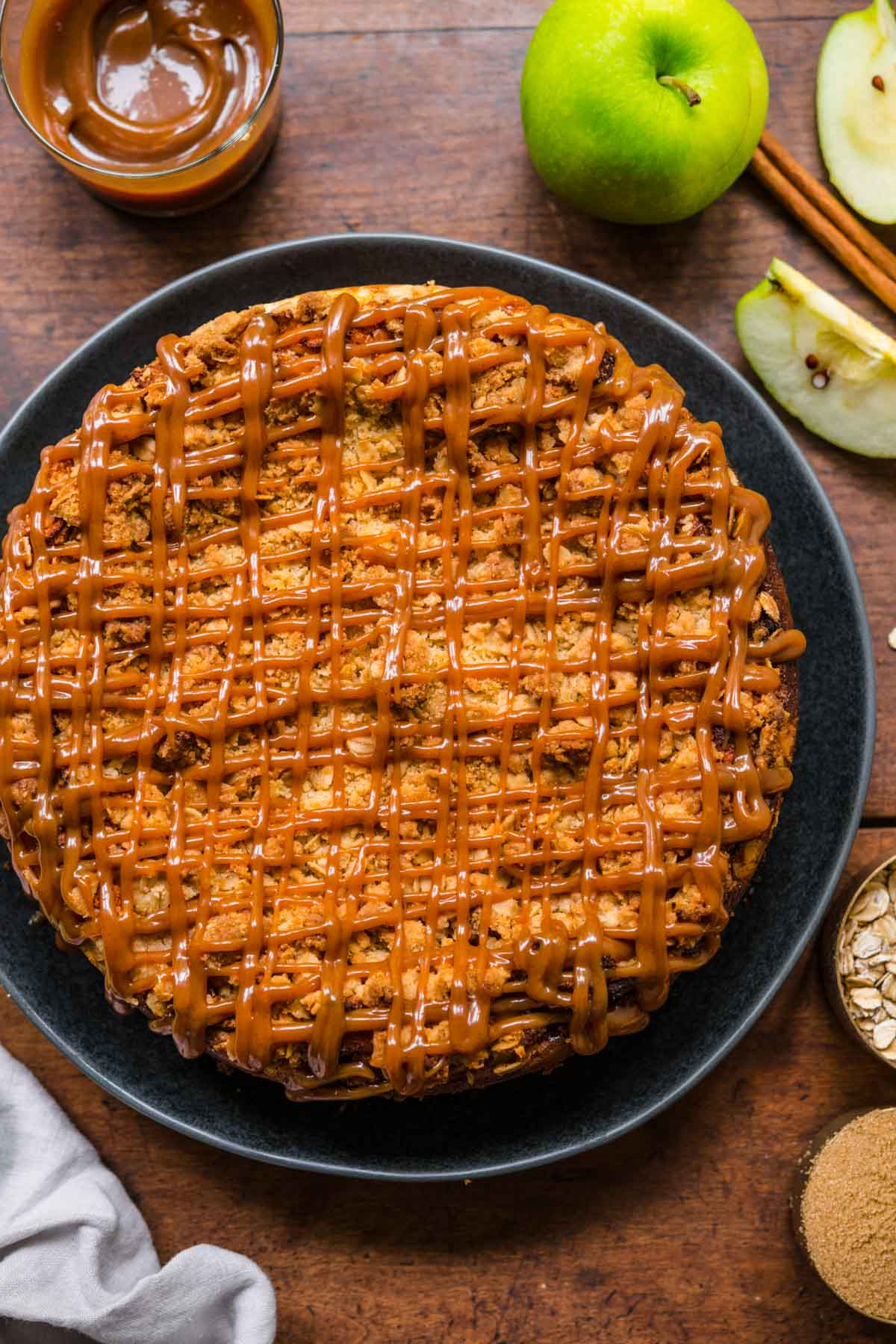 Caramel Apple Crumb Cheesecake on serving plate with caramel drizzle on top