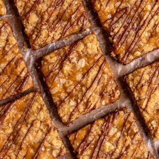 Caramel Chocolate Bars sliced on parchment drizzled with chocolate
