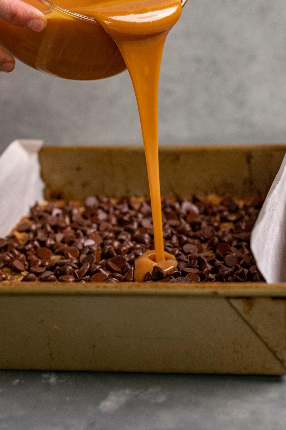 Caramel Chocolate Bars caramel sauce pouring onto chocolate chip layer