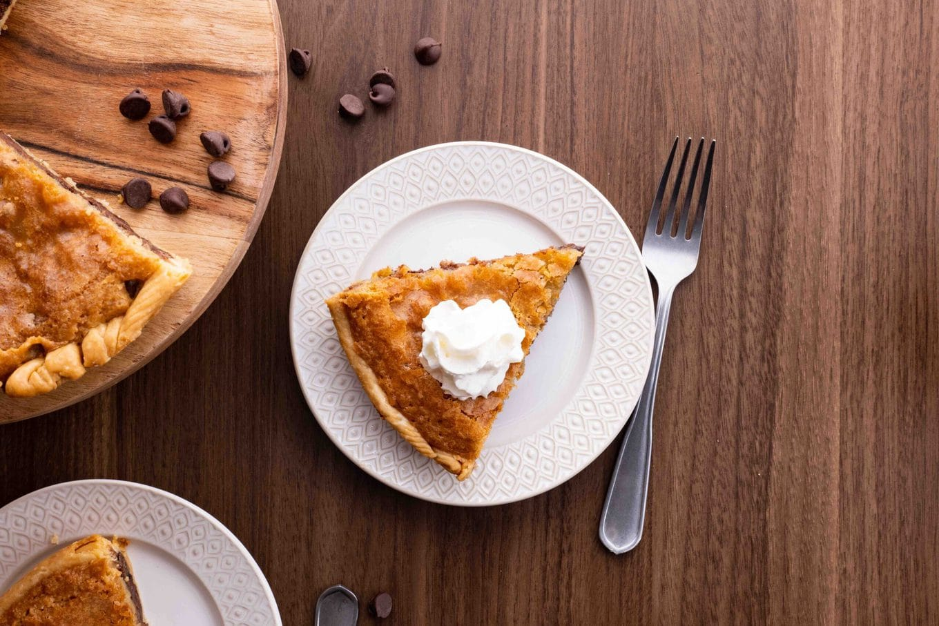 Chocolate Chip Cookie Pie slice on plate with whipped cream