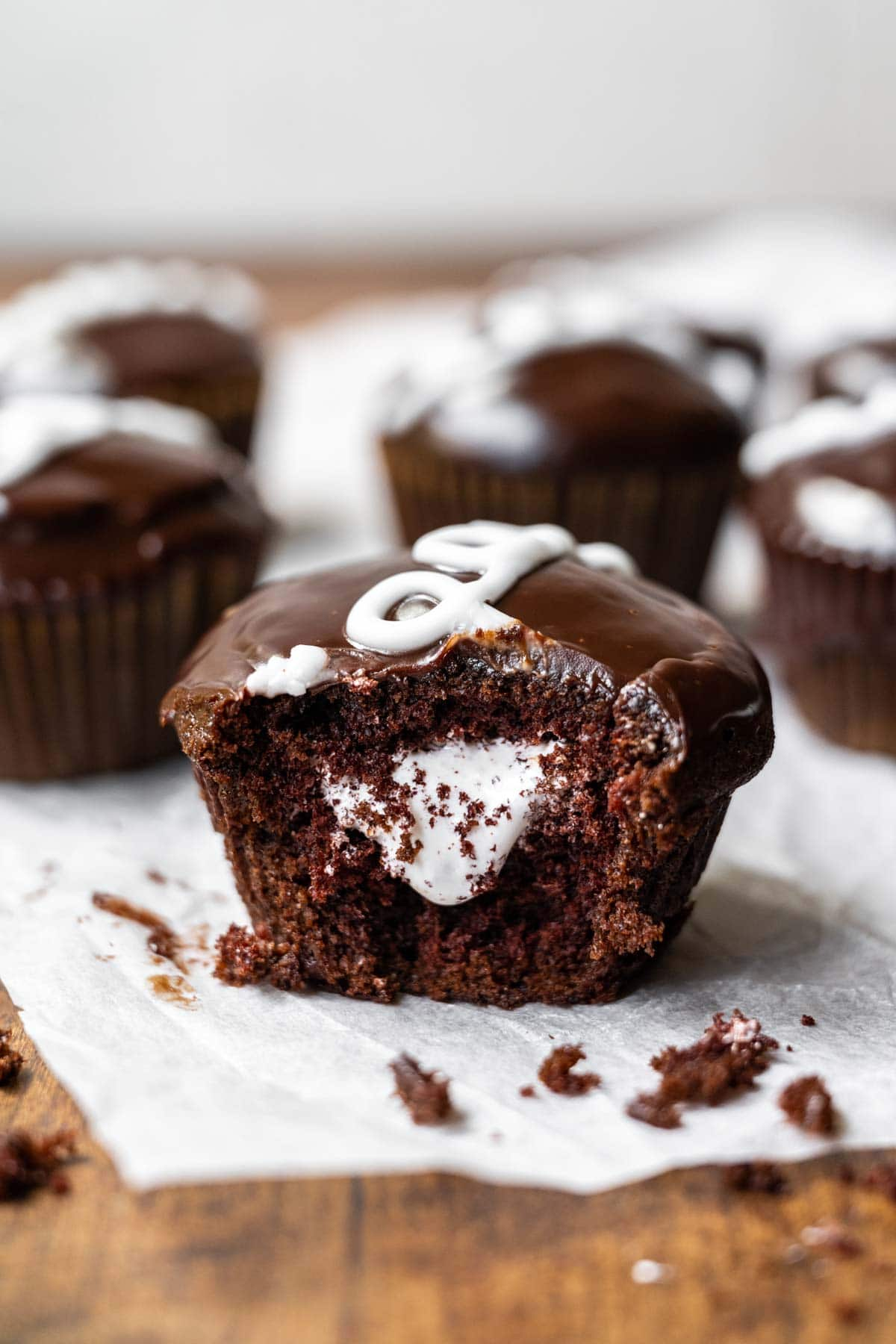 Hostess Cupcakes (Copycat) chocolate cupcake with marshmallow filling and ganache icing with white swirl on parchment paper