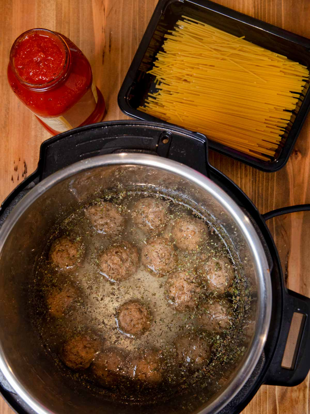 Instant Pot Spaghetti and Meatballs meatballs and water in pressure cooker with pasta and pasta sauce
