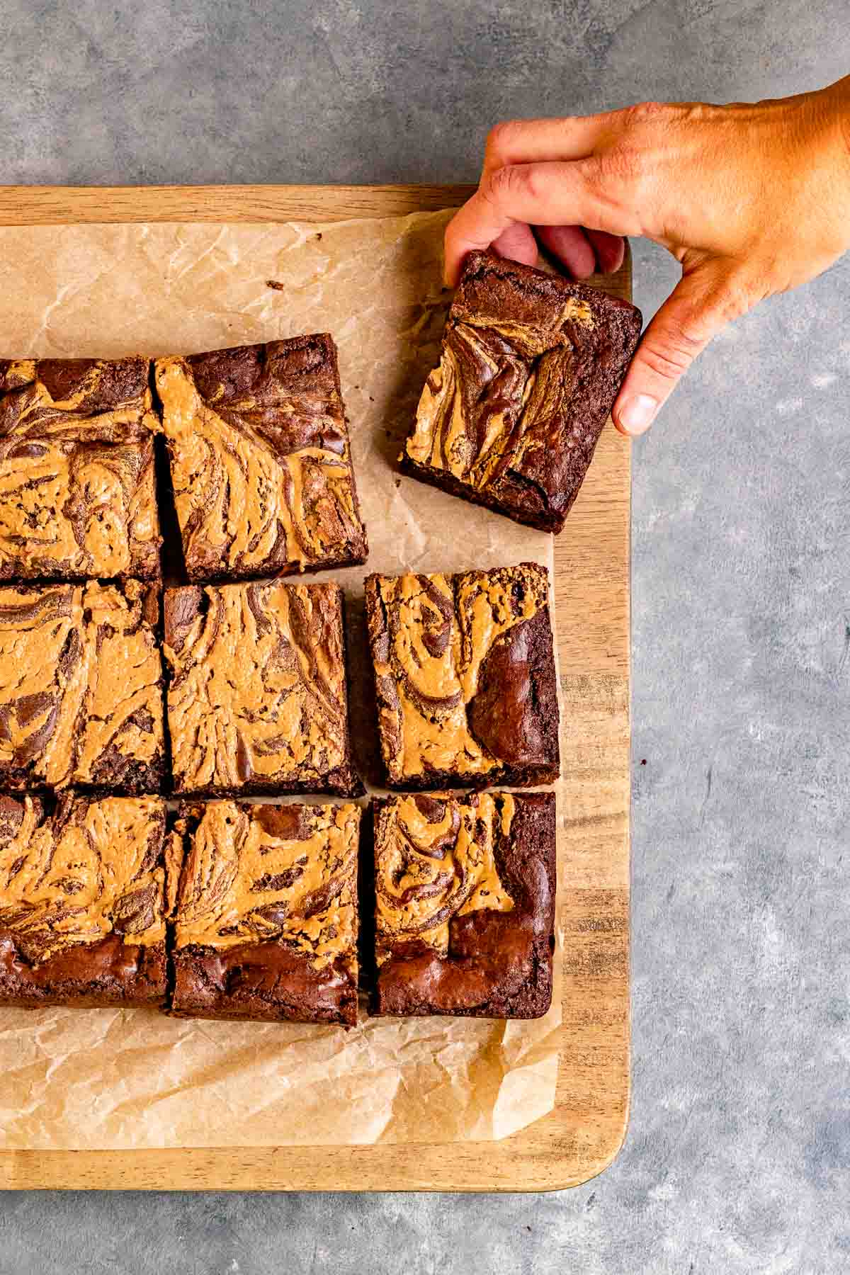 Peanut Butter Swirl Brownies sliced on parchment with hand