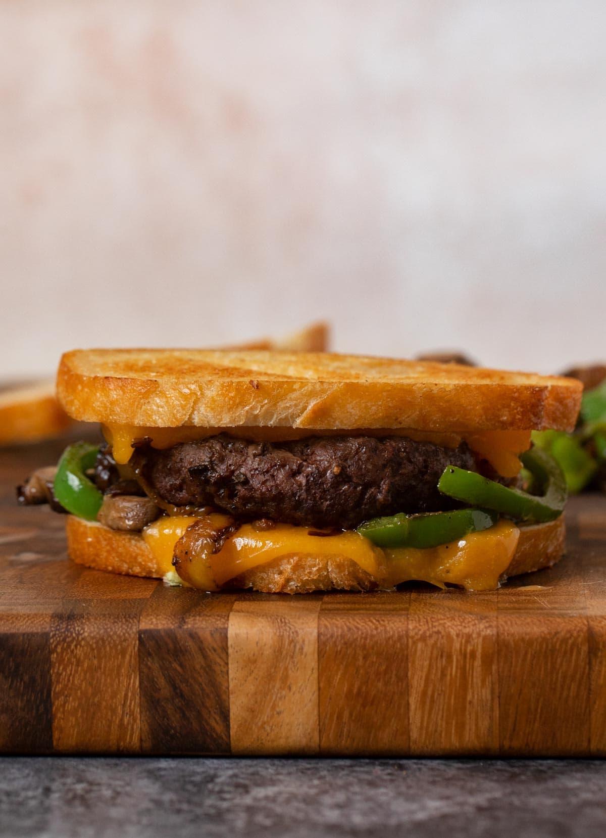 Philly Cheesesteak Patty Melt sandwich on cutting board