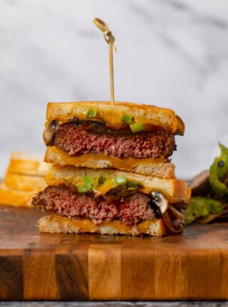 Philly Cheesesteak Patty Melt stacked sandwich halves on cutting board
