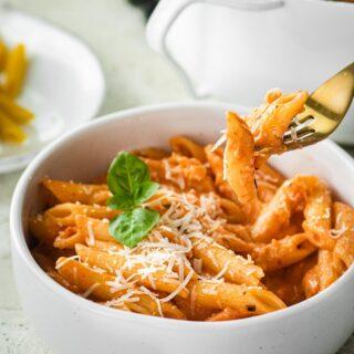 Pink Sauce Pasta in bowl with parmesan and basil garnish