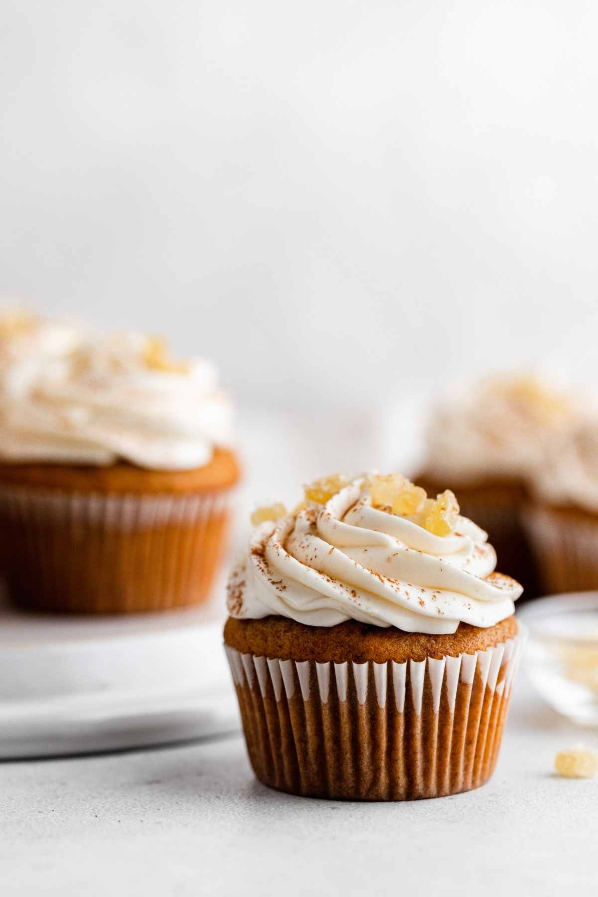 Pumpkin Ginger Cupcakes with cream cheese frosting swirl and candied ginger garnish
