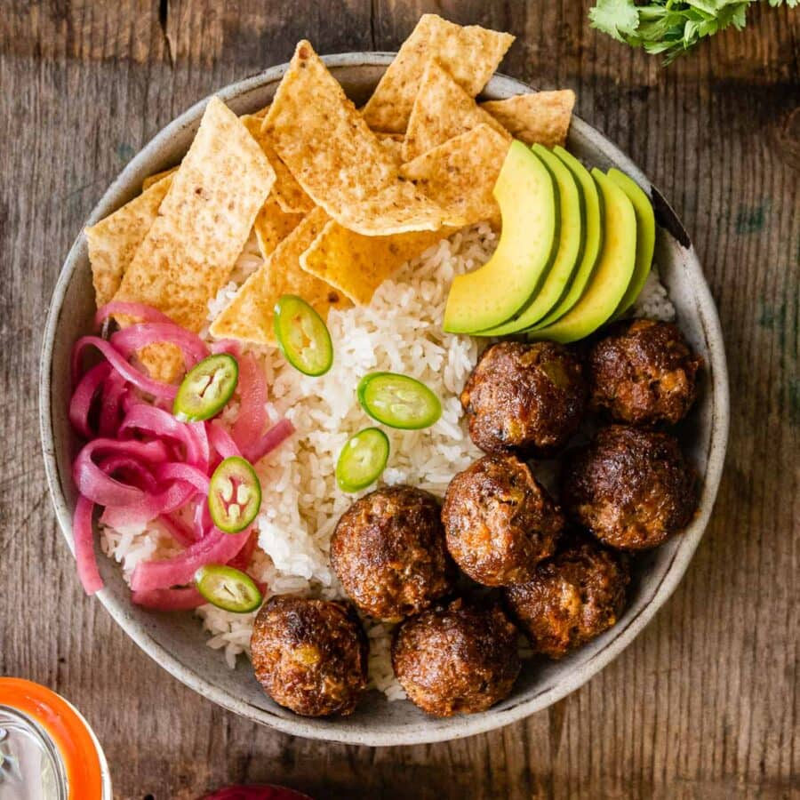 Taco Meatballs in bowl with rice, chips, avocado, jalapeños, and pickled onions