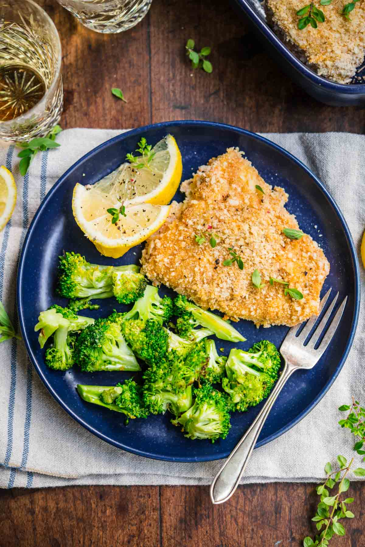 Baked Cod with lemon wedge garnish on plate with broccoli and fork