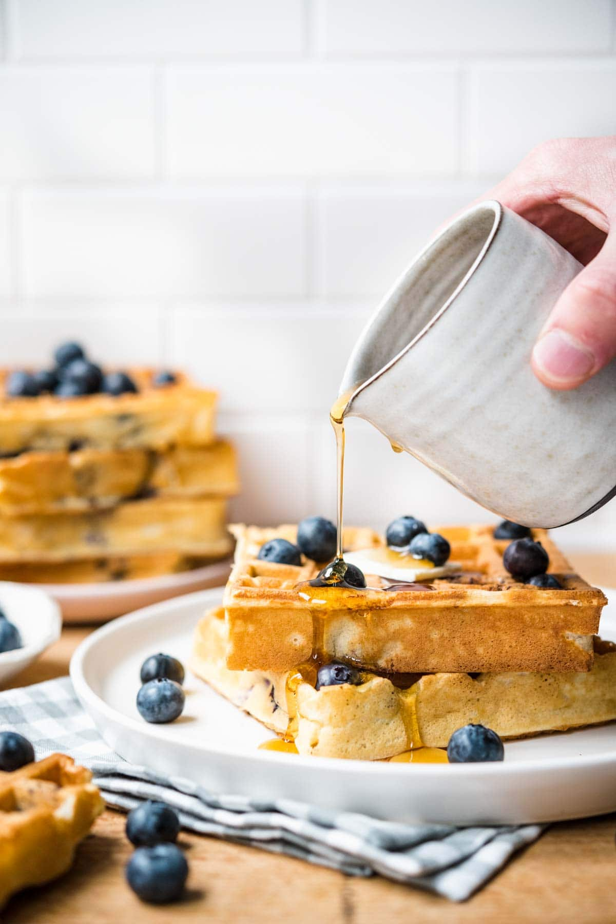 Blueberry Waffles on plate with syrup being poured