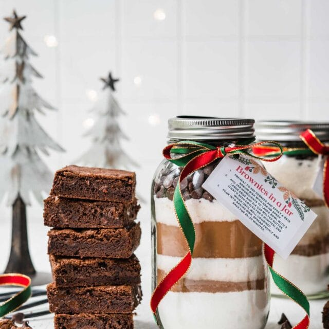 Brownies in a Jar with layered ingredients next to finished baked brownies