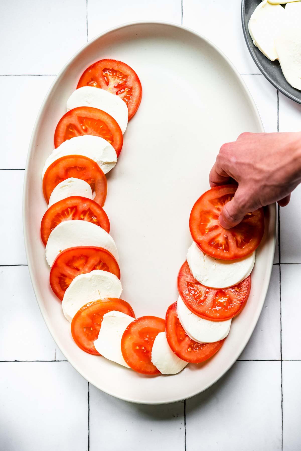 Arranging tomato and mozzarella slices on serving platter for Tomato Mozzarella Salad