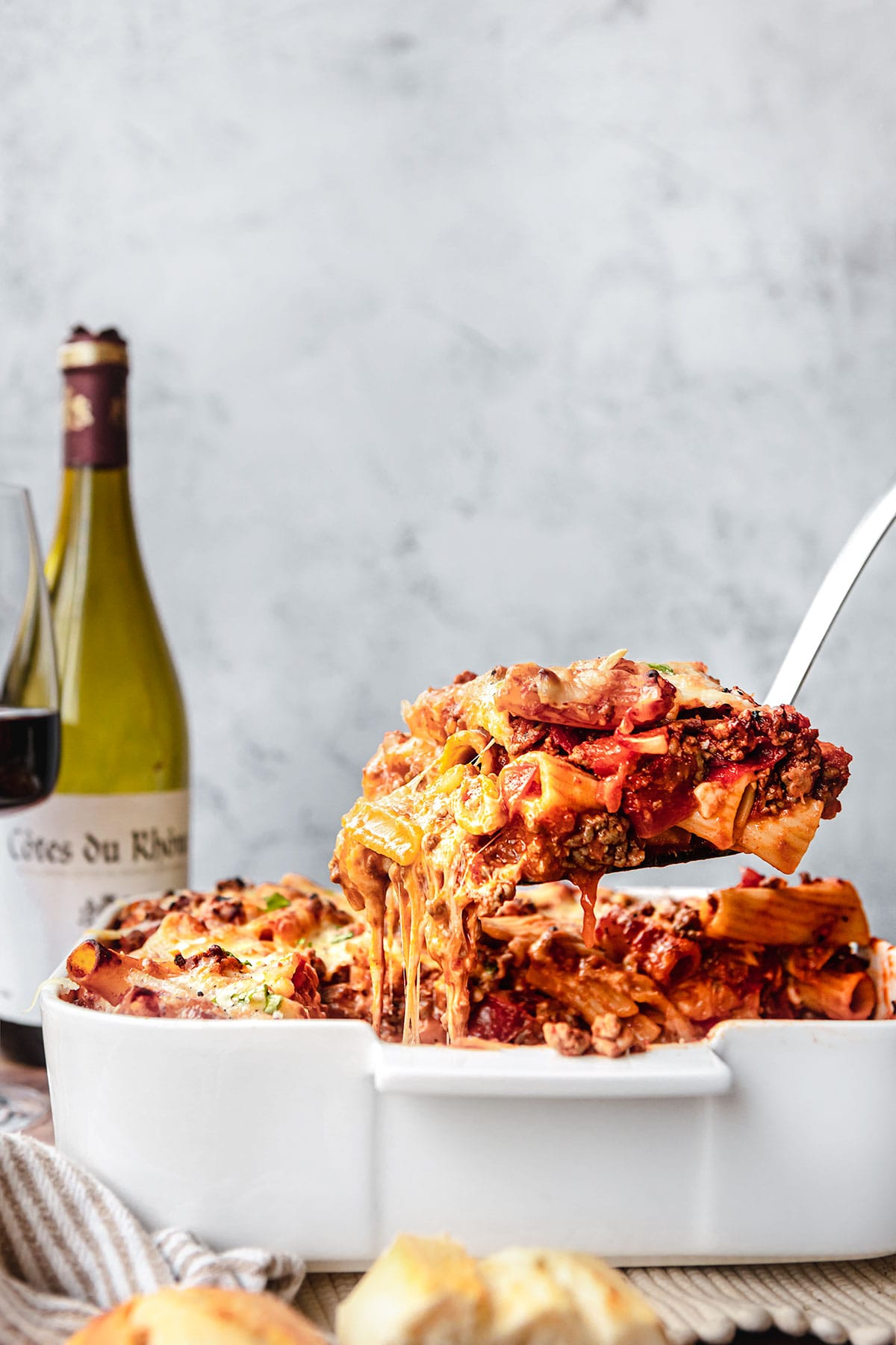 Cheesy Beef Pasta Bake in baking dish with spatula lifting piece out