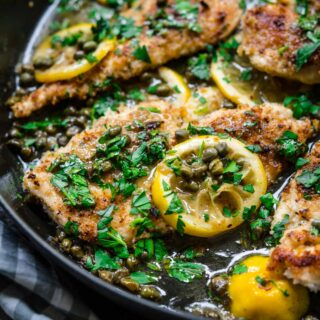 Close up of Chicken Piccata in pan with lemon and parsley