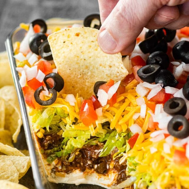 Creamy Layer Taco Dip in pan served with tortilla chips