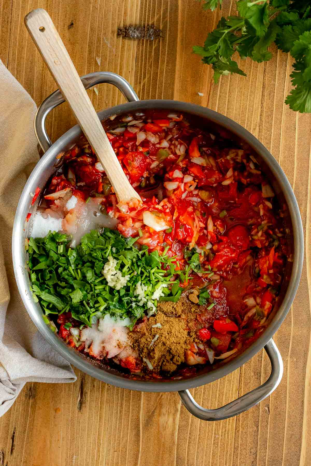 Easy Cooked Jar Salsa in pot with fresh herbs and spices added
