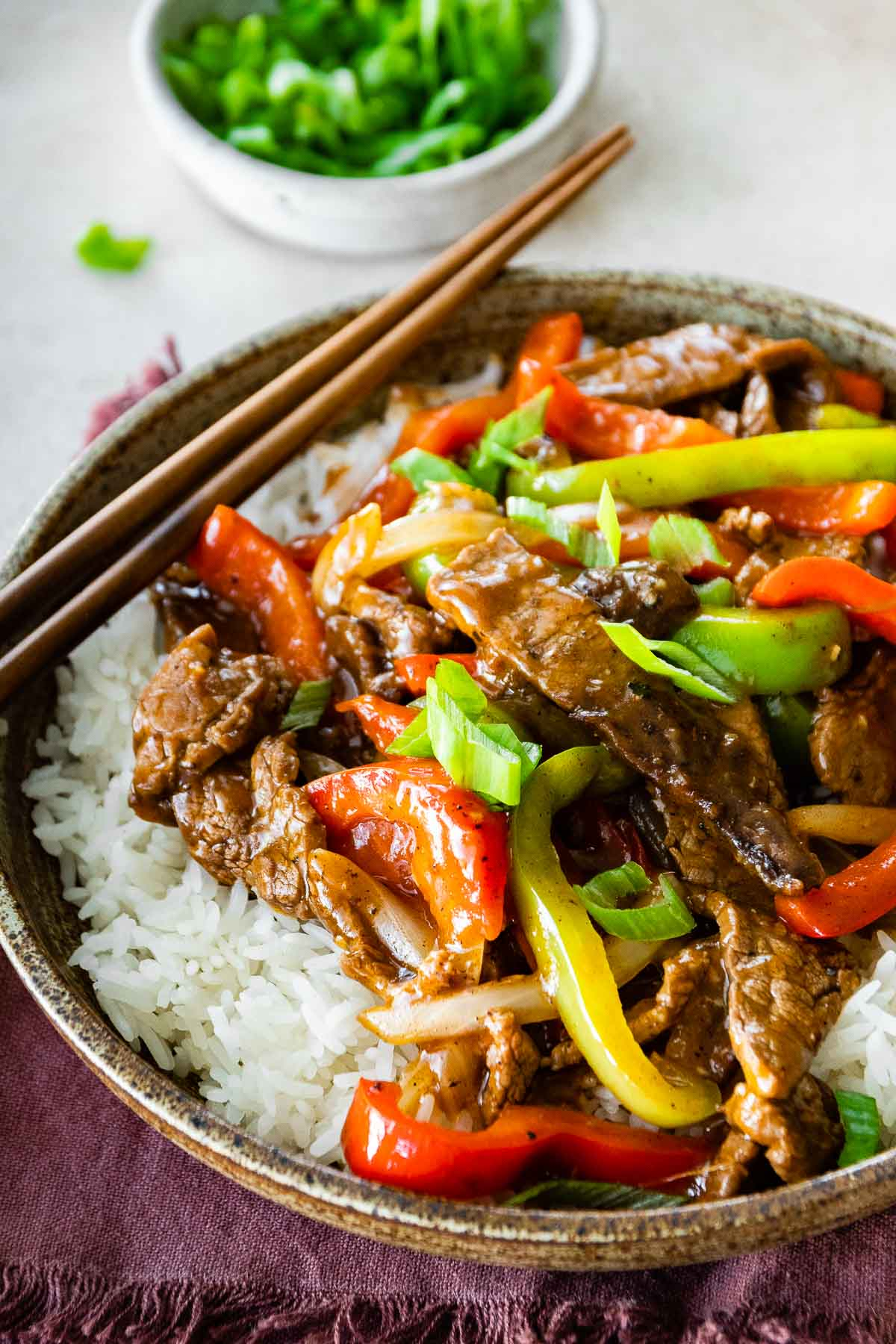 Easy Pepper Steak served over white rice in bowl with chopsticks