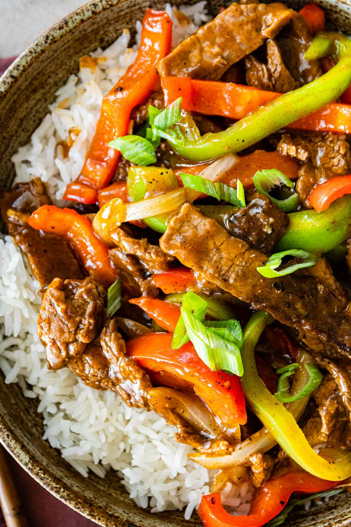 Easy Pepper Steak served over white rice in bowl