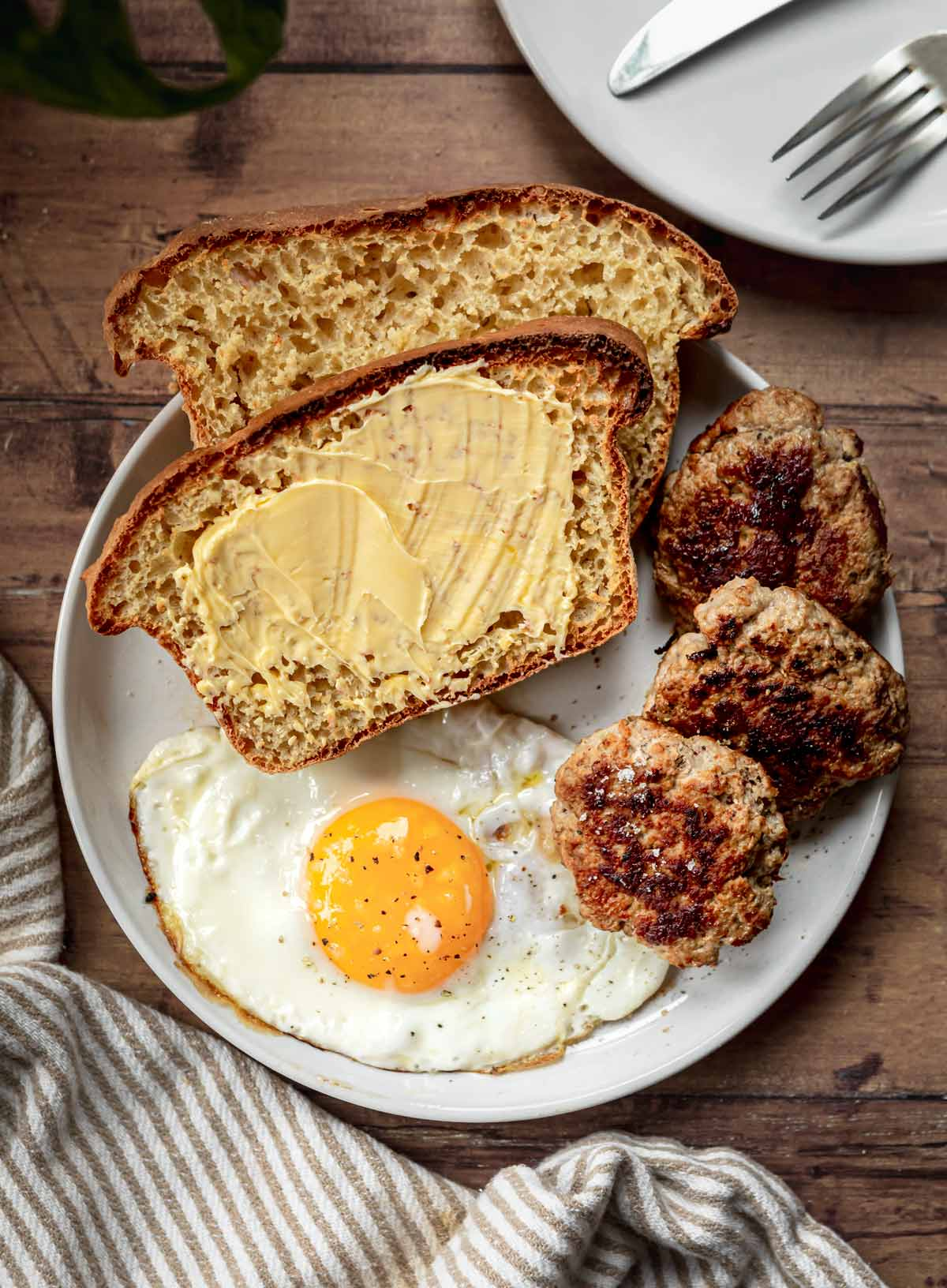 English Muffin Bread slices on plate with butter and breakfast
