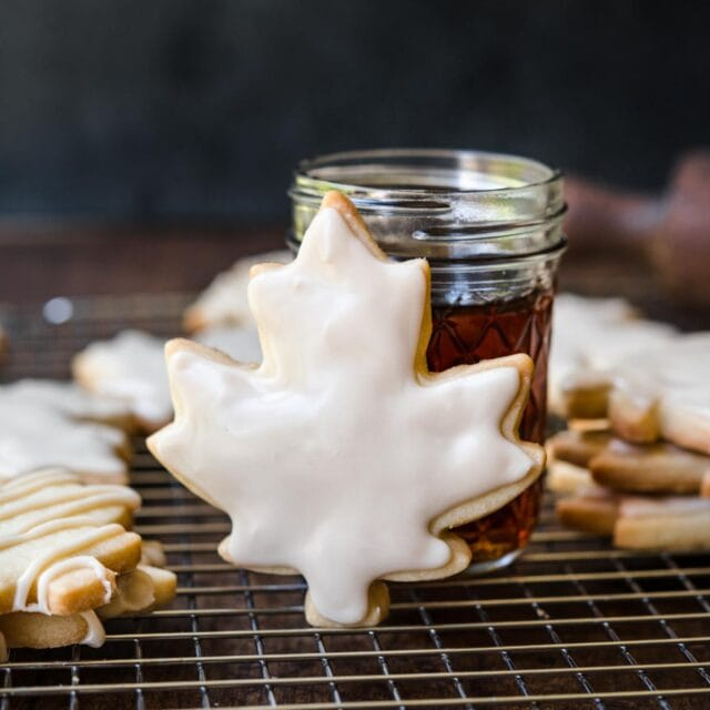 Glazed Maple Shortbread Cookies finished glazed cookies on cooling rack with jar of maple syrup