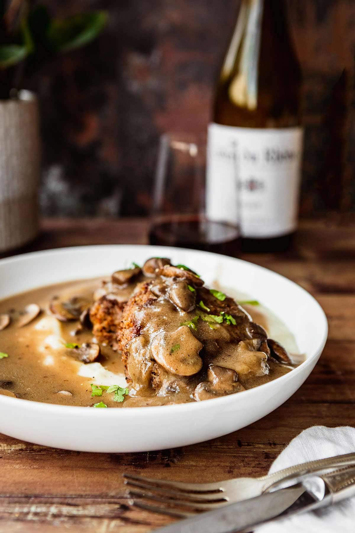Hamburger Steaks with Mushroom Gravy served in a dish over mashed potatoes
