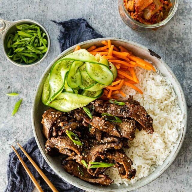 Korean Beef Bulgogi cooked beef slices in serving bowl with white rice, shredded carrots, and sliced cucumbers