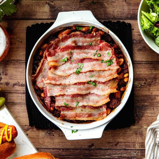 New England Baked Beans in baking dish wtih bacon slices layered on top