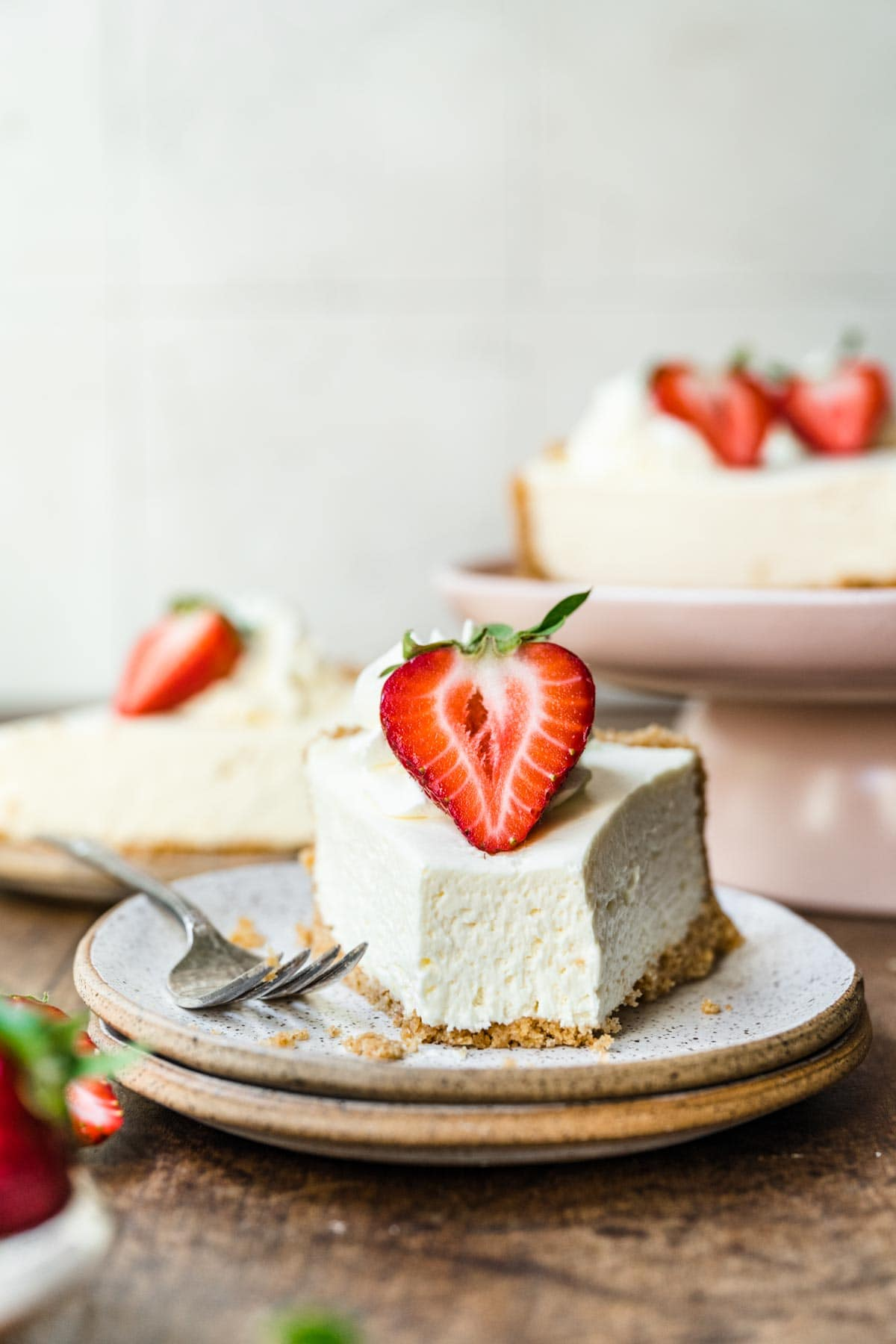 No-Bake Cheesecake sliced with fresh strawberry garnish on plate with fork