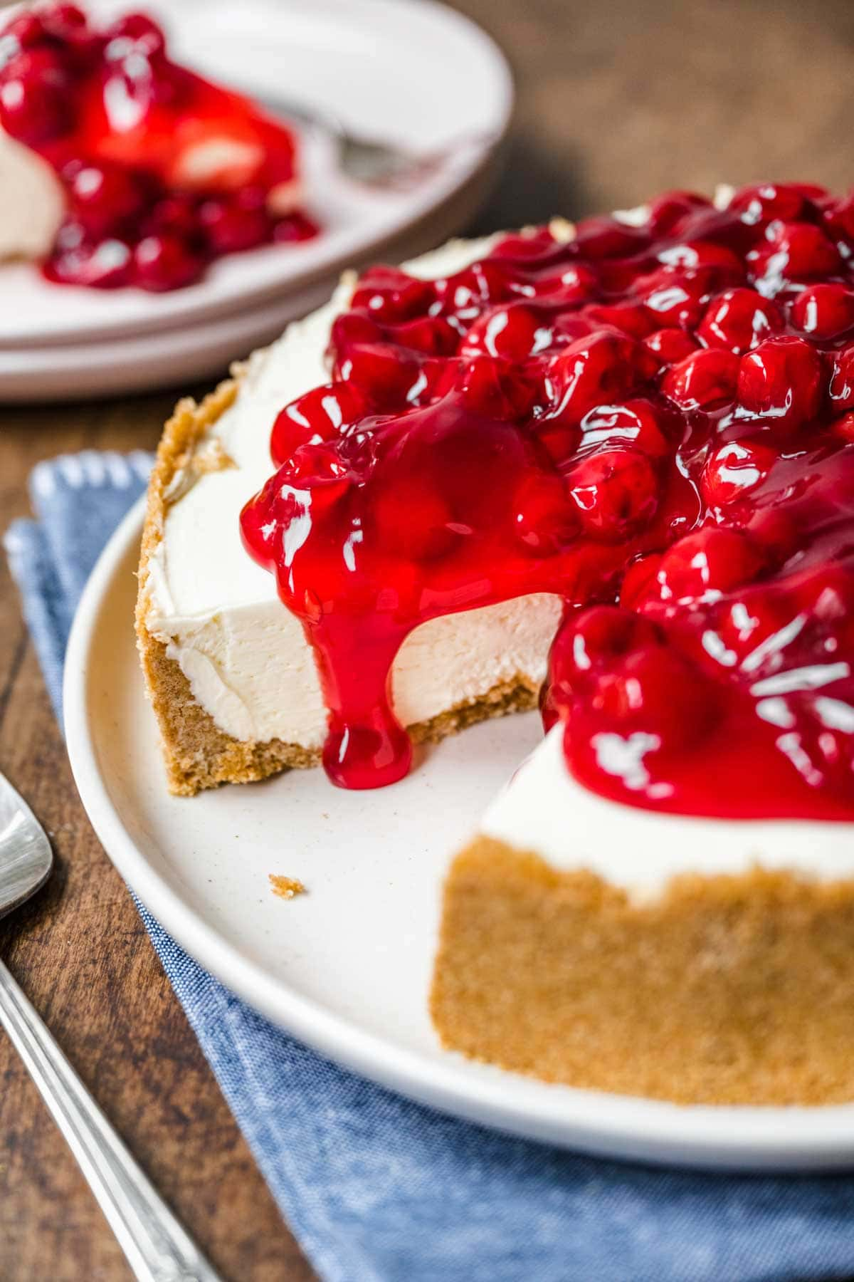 No Bake Cherry Cheesecake on serving plate with slice removed