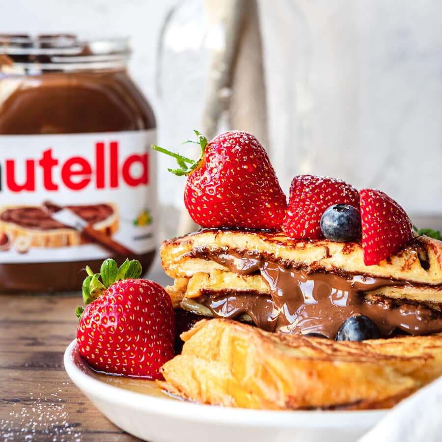 Stuffed Nutella French Toast with berries on top and Nutella Jar