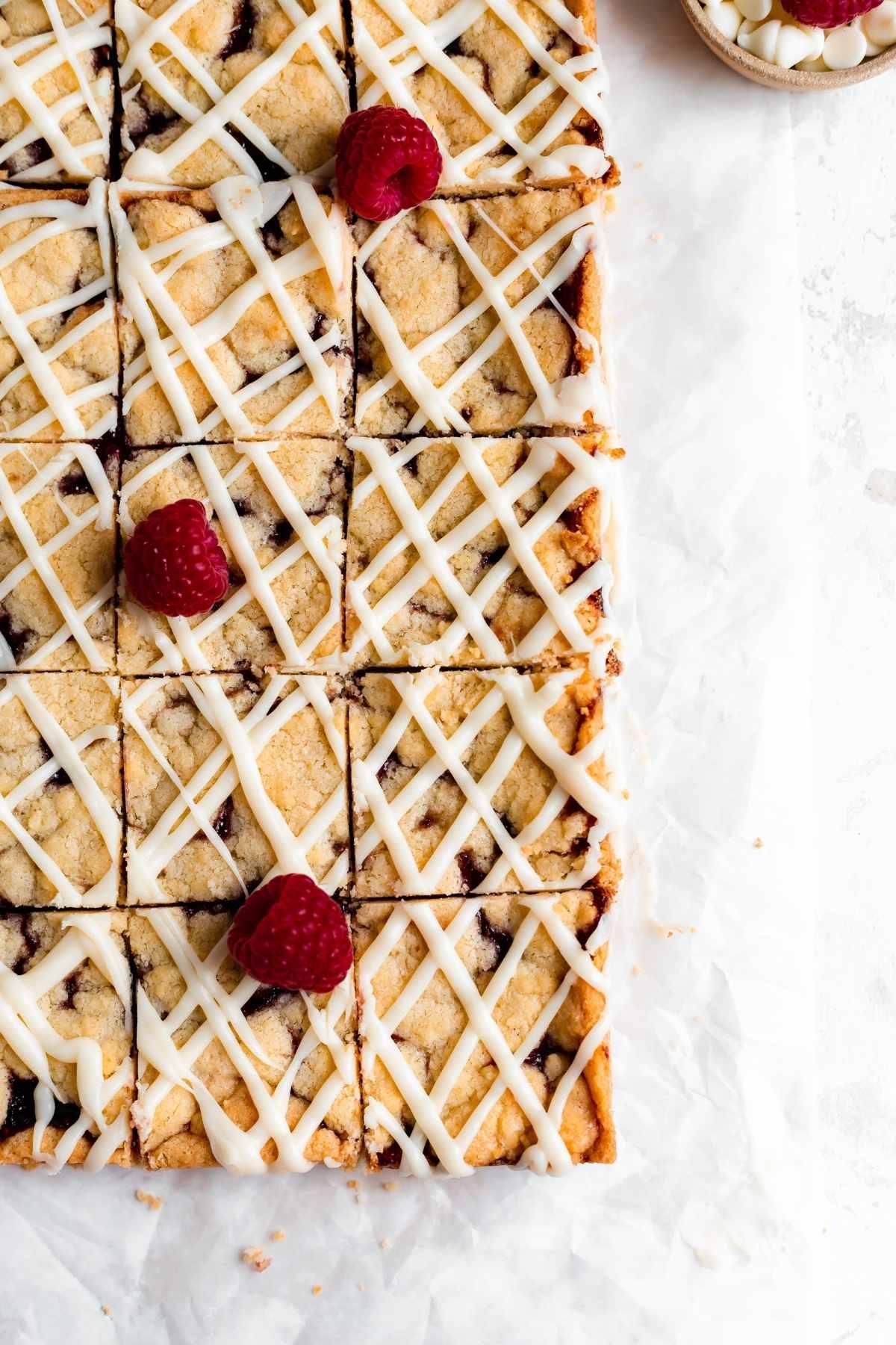 White Chocolate Raspberry Shortbread Bars sliced on parchment with fresh raspberry garnish