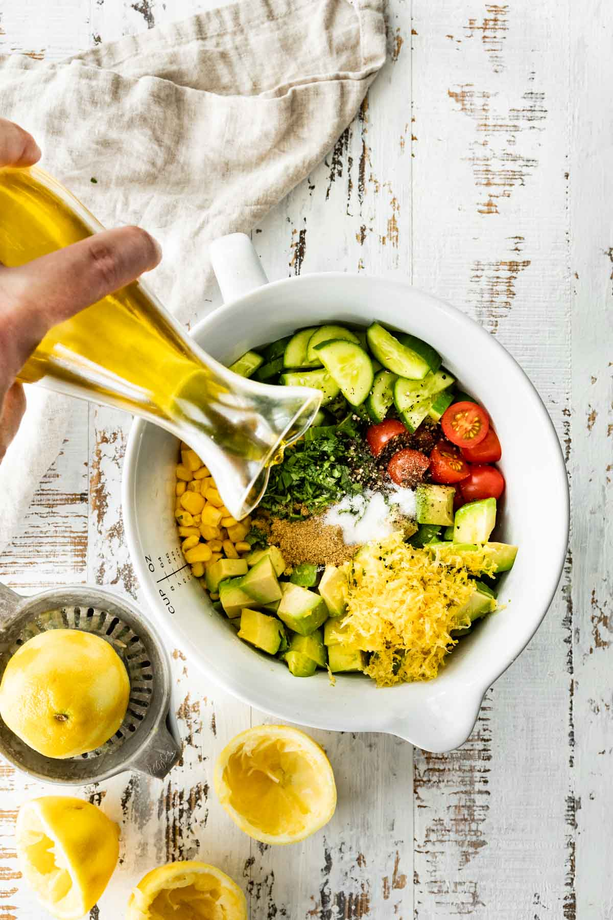Ingredients for Avocado Tomato Corn Salad in mixing bowl with dressing being poured
