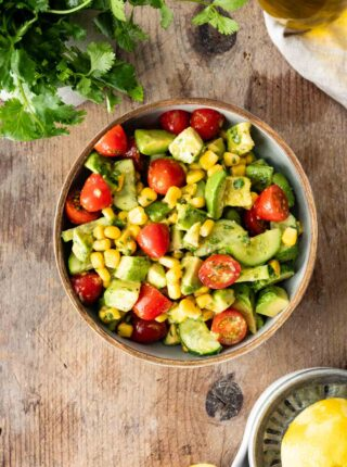 Avocado Tomato Corn Salad in serving bowl on butcher block