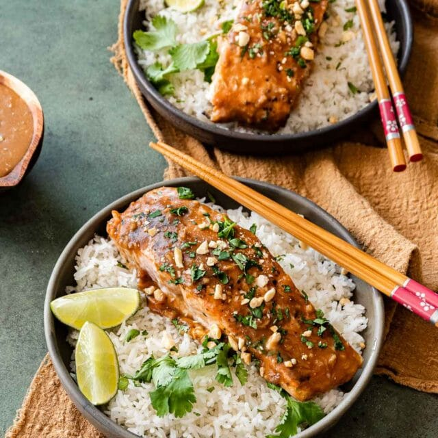 Baked Thai Peanut Salmon in serving bowl with rice and lime wedges