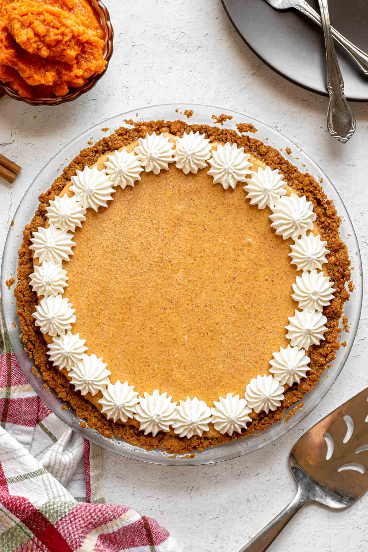 Frozen Pumpkin Ice Cream Pie finished with whip cream stars around crust edge