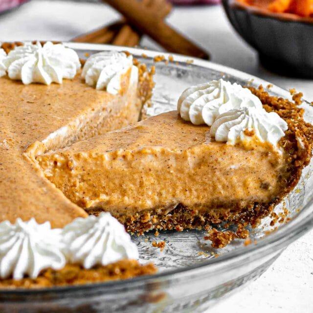 Frozen Pumpkin Ice Cream Pie with whip cream starts around crust edge, sliced in pie plate