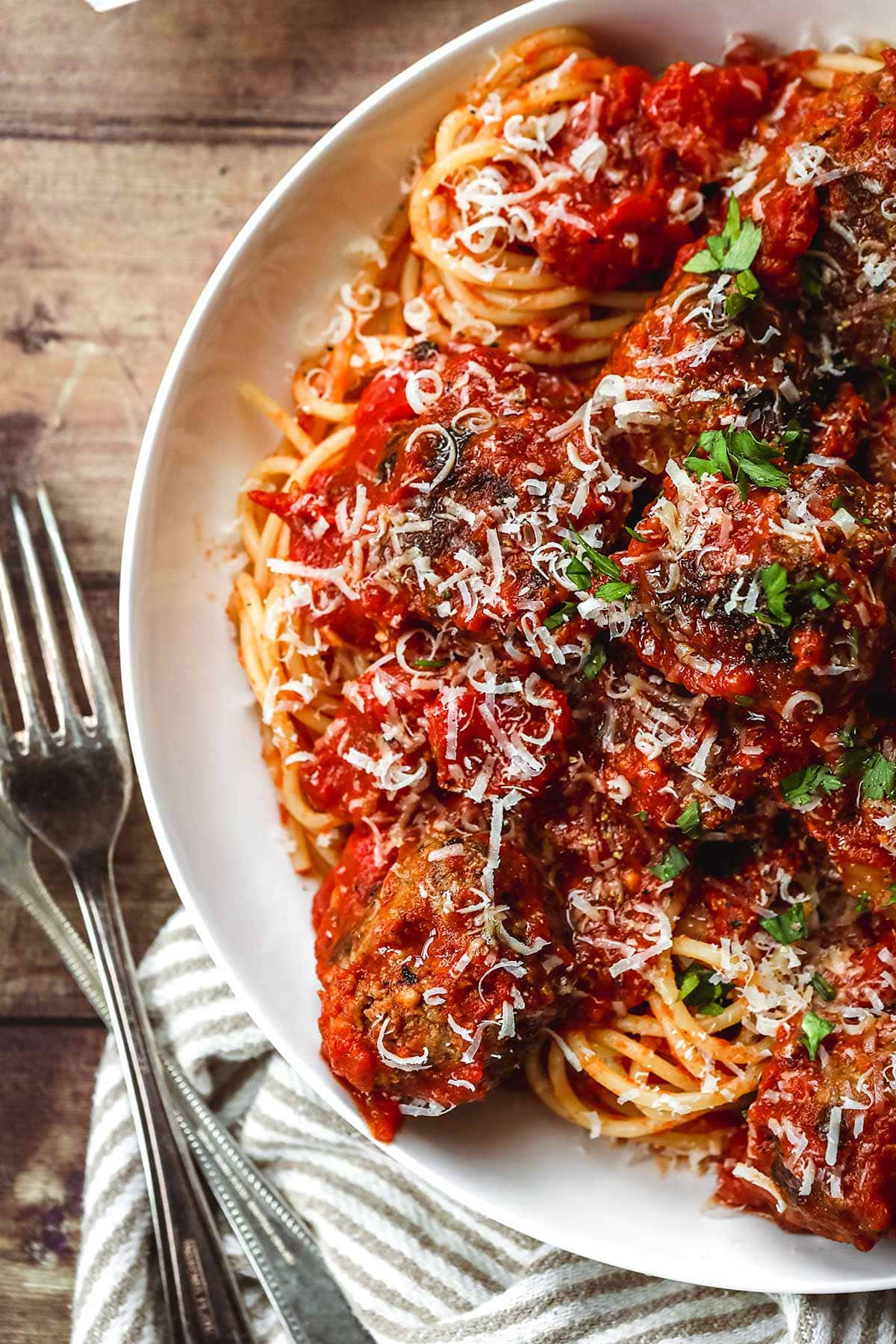 Spaghetti and Meatballs in a bowl with parmesan and parsley topping and fork