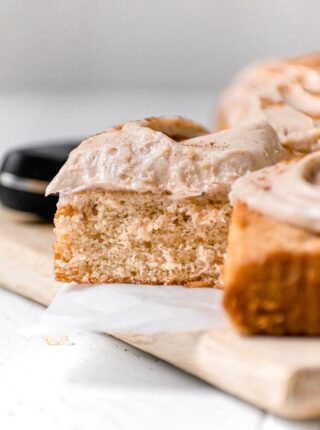 Snickerdoodle Sheet Cake with cinnamon buttercream and cinnamon dusted on top sliced on board