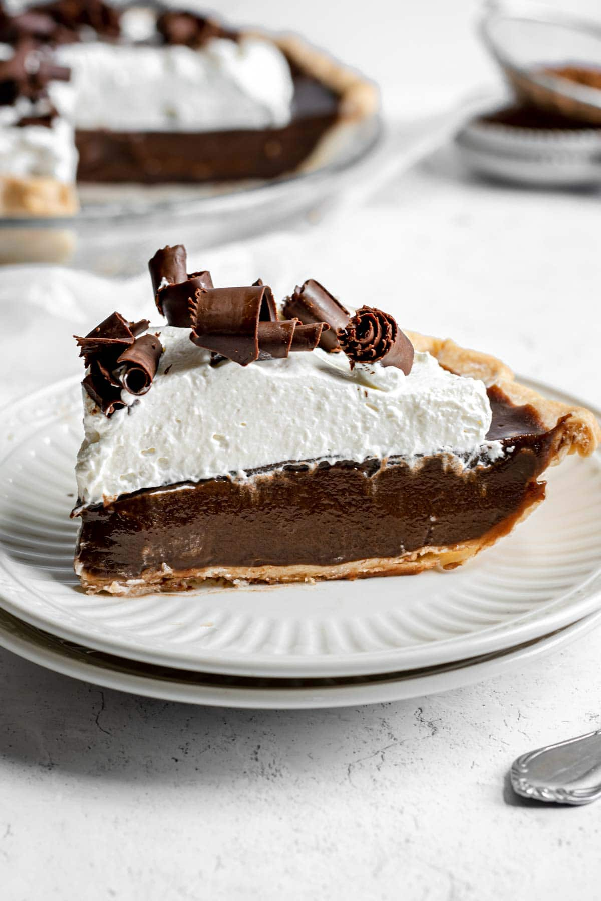 Chocolate Cream Pie with whipped cream and chocolate shavings on serving plate