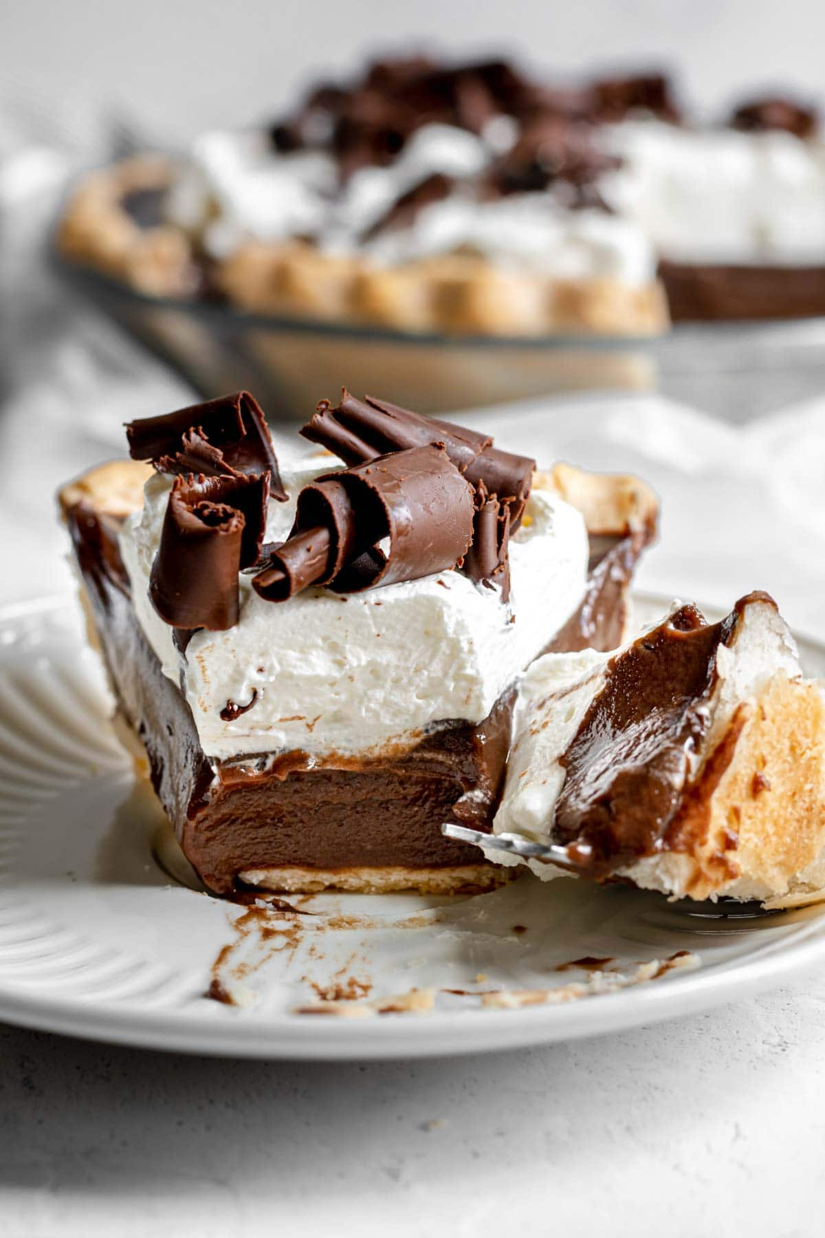 Chocolate Cream Pie with whipped cream and chocolate shavings on serving plate with fork