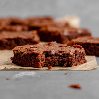 Fudgy Brownies sliced on parchment with bite taken