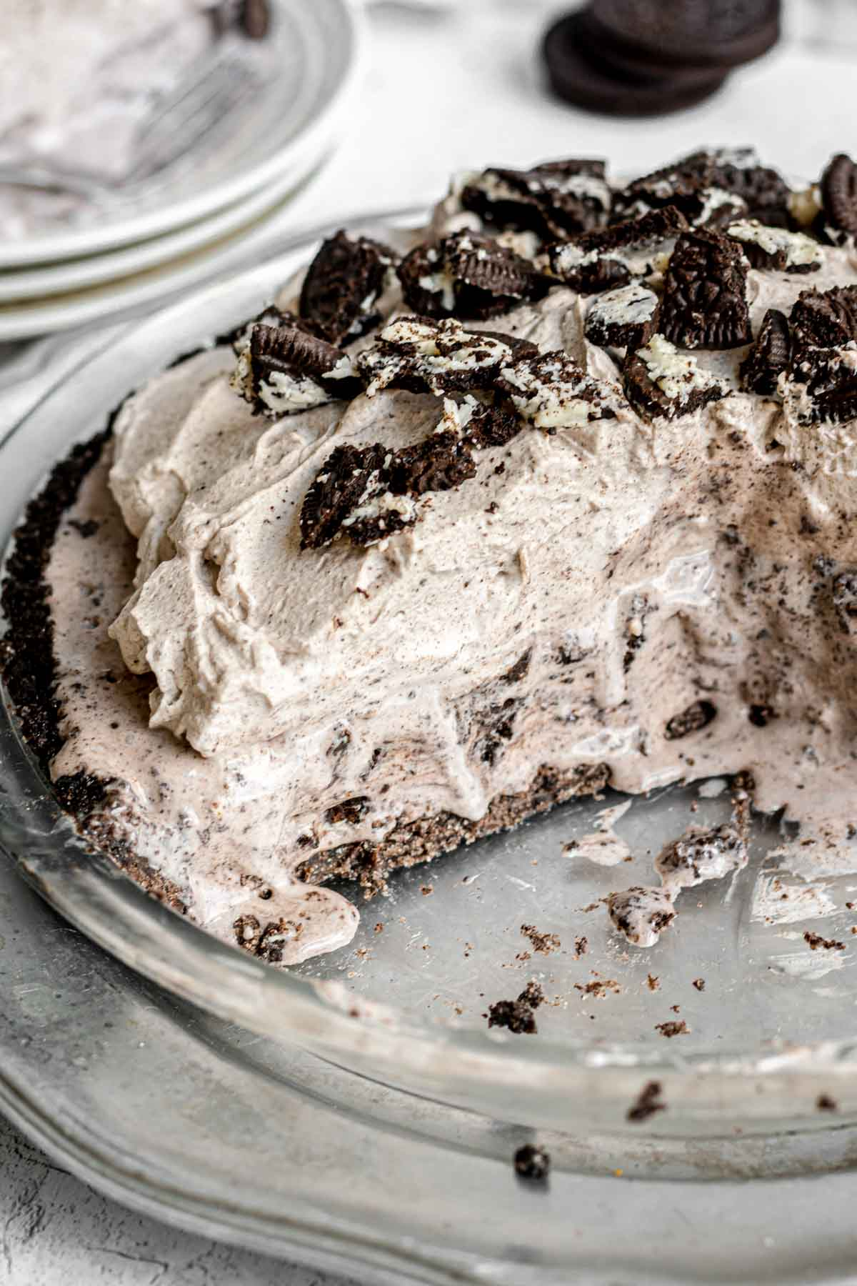 Oreo Ice Cream Pie garnished with whipped cream and oreo pieces in pie plate with slice cut out