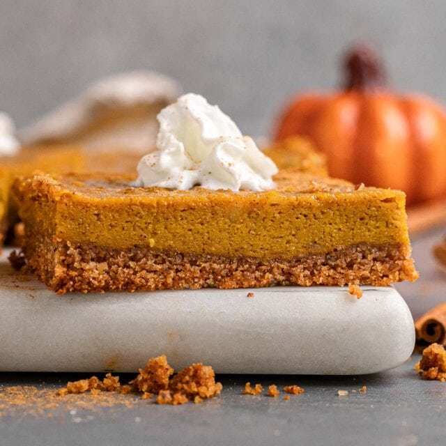 Sliced pumpkin pie bar with whipped cream. Served on a cutting board.
